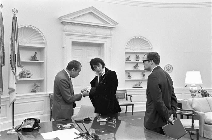 Elvis Presely showing off cufflinks to Pres. Nixon